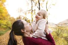 Moeder en dochter op een gang in de herfstbos Stock Fotografie