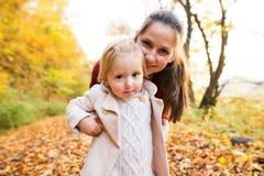 Moeder en dochter op een gang in de herfstbos Stock Afbeeldingen
