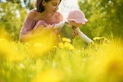 Moeder en dochter op een weide met paardebloemen royalty-vrije stock afbeelding