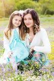 Moeder en dochter op gebied met kleurrijke bloemen stock foto's