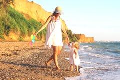 Moeder en dochter op het strand bij zonsondergang stock afbeelding