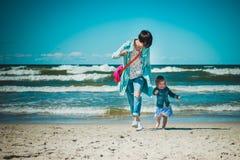 Moeder en dochter op het strand in werking dat wordt gesteld dat Royalty-vrije Stock Foto's