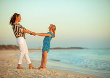 Moeder en dochter op zeekust in avond die prettijd hebben stock afbeelding