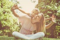 Moeder en dochter in openlucht in een weide Moeder die haar DA vervoeren royalty-vrije stock foto