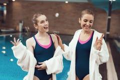 Moeder en dochter in robes die zich dichtbij pool bij de gymnastiek bevinden Zij kijken gelukkig, modieus en geschikt stock foto's