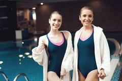 Moeder en dochter in robes die zich dichtbij pool bij de gymnastiek bevinden Zij kijken gelukkig, modieus en geschikt royalty-vrije stock fotografie