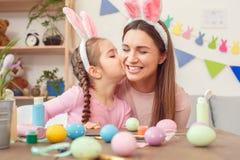 Moeder en dochter samen thuis de voorbereiding van Pasen in konijntjesoren die meisjes kussend mamma zitten royalty-vrije stock foto