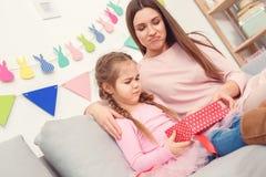 Moeder en dochter samen thuis de zittingsmeisje die van het vieringsconcept binnen huidige ongelukkige doos kijken royalty-vrije stock afbeelding