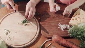 Moeder en dochter scherp ui en knoflook op houten raad stock video