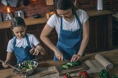 Moeder en Dochter Scherpe Groenten voor Salade stock afbeelding