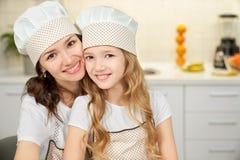 Moeder en dochter in schorten en chef-kokhoeden die, het glimlachen stellen stock foto's