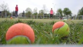 Moeder en dochter speeltennis op de tennisbaan, defocus, achtergrond, opleiding stock video