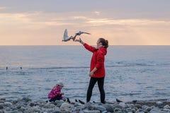 Moeder en dochter voedende zeemeeuwen op de overzeese kust royalty-vrije stock foto