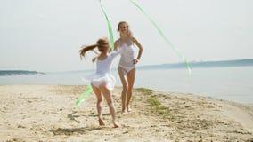Moeder en dochter in witte badpakken die met gymnastiek- lint op een zandig strand dansen De zomer, dageraad stock videobeelden