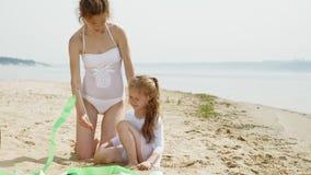 Moeder en dochter in witte badpakken die met gymnastiek- lint op een zandig strand dansen De zomer, dageraad stock video