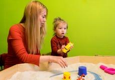 Moeder en dochter witte Europese mensen die studies van vroege ontwikkeling met zand in de zandbak en meer ontwikkelen Stock Foto's