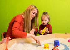 Moeder en dochter witte Europese mensen die studies van vroege ontwikkeling met zand in de zandbak en meer ontwikkelen Stock Afbeelding