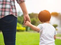 Moeder en dochterholdingshanden die in het park lopen Jong geitje en M stock foto's
