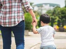 Moeder en dochterholdingshanden die in het park lopen Jong geitje en M royalty-vrije stock fotografie