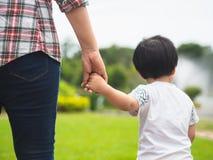 Moeder en dochterholdingshanden die in het park lopen Jong geitje en M stock afbeelding