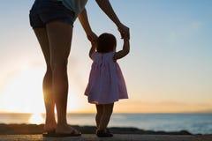 Moeder en dochterholdingshanden, die op de zonsondergang samen op een strand letten stock afbeelding