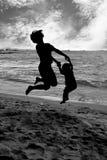 Moeder en dochterholdingshanden en samen het springen royalty-vrije stock fotografie