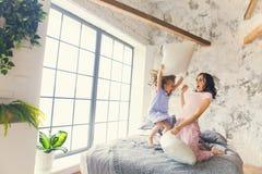 Moeder en dochterhoofdkussenstrijd in slaapkamer royalty-vrije stock fotografie