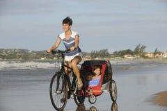 Moeder en dochters die een fiets berijden op het strand Stock Foto's