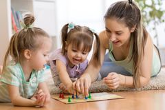 Moeder en dochters die in een speelkamer zitten, een spel van Ludo spelen en van hun tijd samen genieten stock foto