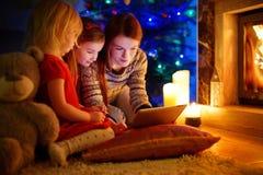 Moeder en dochters die een tablet gebruiken door een open haard op Kerstmis stock foto's