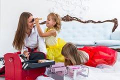 Moeder en dochters die make-up doen Stock Afbeeldingen
