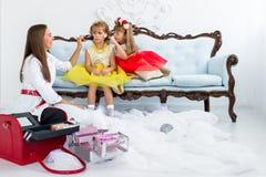 Moeder en dochters die make-up doen Stock Fotografie