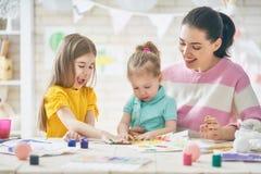 Moeder en dochters die samen schilderen Stock Afbeeldingen
