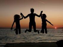 Moeder en dochters die in zonsondergang springen Stock Foto's