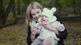 Moeder en dochterspel in de herfstpark Ouder en babygang in het bos op een dalingsdag Baby het spelen in openlucht met stock videobeelden