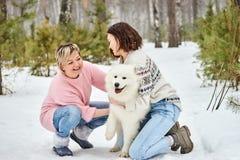 Moeder en dochterspel met hond in de winter het bos stock fotografie