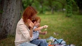 Moeder en dochterspel met kamille openlucht stock footage