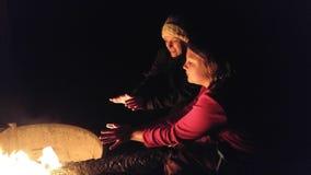 Moeder en Dochterzitting door een kampvuur op een koude nacht Royalty-vrije Stock Afbeelding