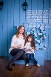 Moeder en dochterzitting in een mooi binnenland Royalty-vrije Stock Fotografie