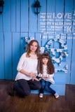 Moeder en dochterzitting in een mooi binnenland Royalty-vrije Stock Afbeeldingen