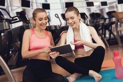 Moeder en dochterzitting op mat die tablet gebruiken bij de gymnastiek Zij kijken gelukkig, modieus en geschikt royalty-vrije stock afbeeldingen