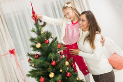 Moeder en Dughter die Kerstboom verfraaien Stock Afbeeldingen