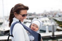 Moeder en een glimlachende leuke babyjongen in een babydrager Stock Fotografie