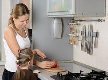 Moeder en haar appel van de dochterbesnoeiing in de keuken Stock Afbeeldingen