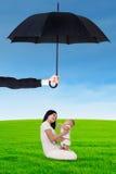 Moeder en haar baby die onder paraplu bij gebied spelen Stock Fotografie
