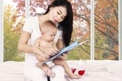 Moeder en haar baby gelezen verhaalboek Stock Afbeeldingen