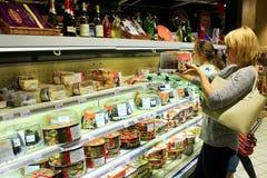 Moeder en haar dochter choicing cake op planken van supermarkt royalty-vrije stock foto's