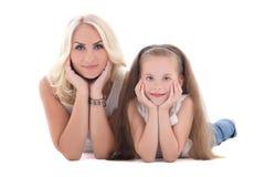 Moeder en haar dochter die die op de vloer liggen op wit wordt geïsoleerd Stock Foto