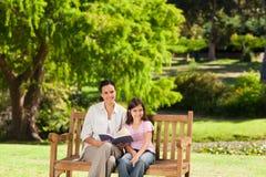 Moeder en haar dochter die een boek lezen Stock Foto's