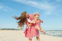 Moeder en haar dochter die pret op het strand hebben Stock Afbeeldingen